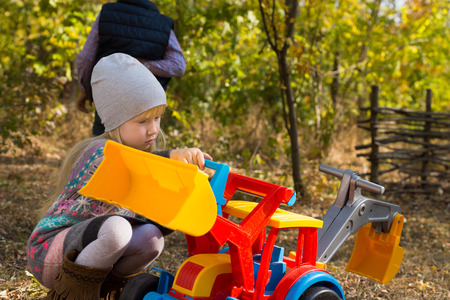 front end loader: Pretty little girl in autumn fashion playing with colorful multicolored plastic toy a front end loader outdoors in the garden