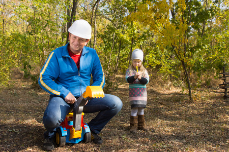 front end loader: Father wearing a hardhat riding on his childs colorful plastic toy front end loader watched anxiously by a cute anxious little girl with her hands clasped