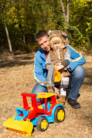 front end loader: Cute little girl in a spotted cat suit posing in the arms of her kneeling father outdoors in q park with a large colorful plastic construction toy with a front end loader