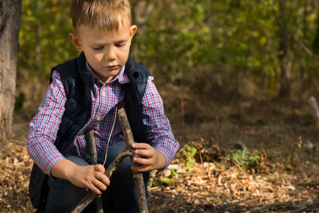 tepee: Handsome little boy building a small tepee from wooden twigs and branches as he plays outdoors in woodland