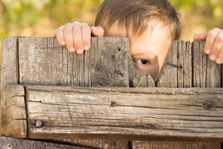 Little boy playing peek a boo through a gap in a broken plank in a rustic wooden gate looking at the camera with one eye