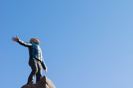 outspread: Exuberant young man on top of an old stone wall standing with his arms outspread shouting at the sun against a clear blue sky with copyspace, view looking up from below Stock Photo