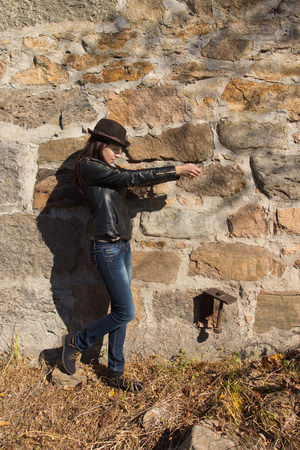 authoritative woman: Slender chic young woman standing sideways in front of a stone wall in her leather jacket and trendy hat in the sunshine, copyspace above Stock Photo