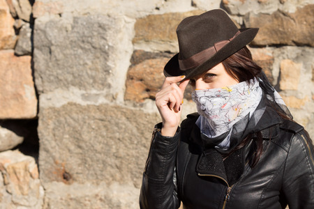 concealing: Stylish young woman bandit doffing her hat and looking at the camera with a scarf tied around her face concealing her features, against a stone wall with copyspace
