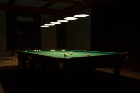 billiards room: Billiard Balls Scattered on Pool Table in Empty Dimly Lit Pool Hall Stock Photo