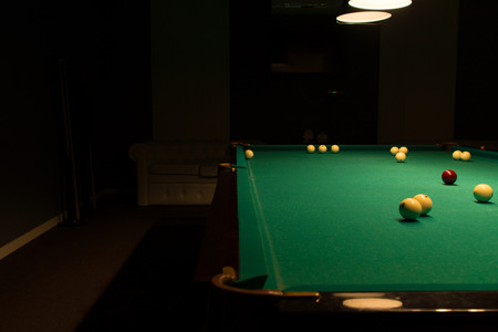 dimly: Billiard Balls Scattered on Pool Table in Empty Dimly Lit Pool Hall Stock Photo