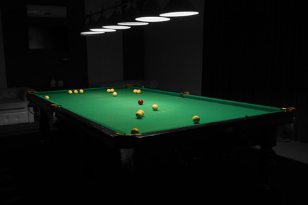 Billiard Balls Scattered on Pool Table in Empty Dimly Lit Pool Hall Stock Photo