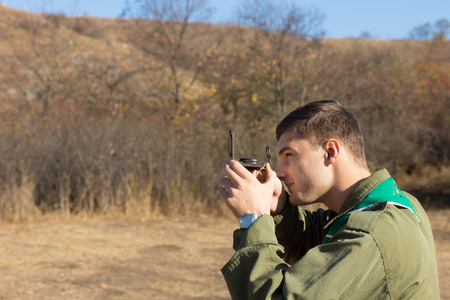 Scout or ranger taking a sighting with a compass lining it up with his eye as he traverses the wilderness using it for navigation Stock Photo