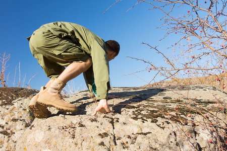 Side View of a Young Male Scout Climbing a Big Rock at the Field on a Tropical Climate with Light Blue Sky Background. photo
