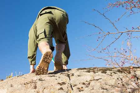Rear View of White Boy Scout in Uniform Climbing a Big Rock on A Sunny Climate. Captured with Light Blue Sky Background. photo