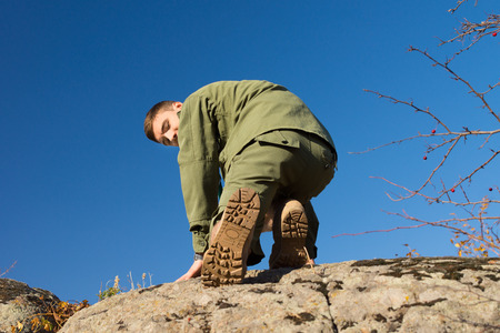 Young Handsome Boys Scout Climbing on a Big Rock While Looking at the Camera. Captured on a Blue Sky Background. photo