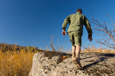 Rear View of White Boy Scout Walking on Old Big Rock at Camp Area on a Blue Sky Background. photo