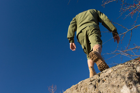 Rear View of Young Male Scout Climbing on Old Rock with Blue Sky Background. photo