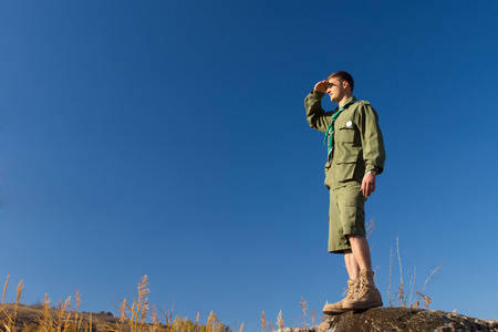 Young Male Scout Standing on Big Rock Observing the Field at the Camp Area on a Blue Sky Background. photo