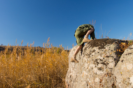 Boys Scout Climbing on Big Old Rock at the Brown Field Under a Blue Sky During Autumn Season. photo