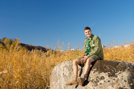 Boy Scout Resting on Large Rock at the Camp Area While Looking at the Camera, Under a Blue Sky Above. photo