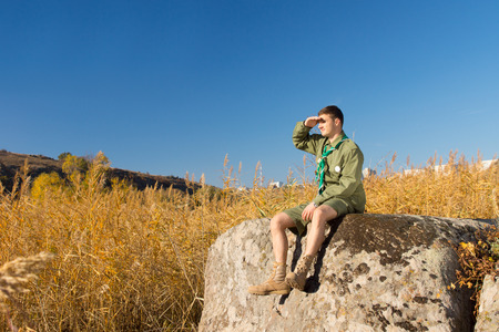 conservationist: Male Scout Sitting on Huge Rock Surveying the Wide Landscape at the Camp Area with Tall Brown Grasses.