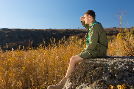 conservationist: Side View of Young White Boy Scout Sitting on Old Big Rock Watching Over the Wide Brown Field on an Autumn Season.