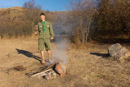 making a fire: Scout or ranger making a cooking fire in a clearing in the grassland vegetation to cook his lunch standing smiling at the camera