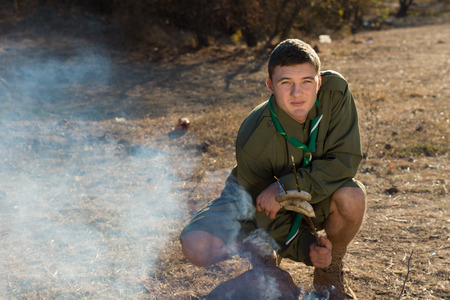 making a fire: Young Boy Scout in Uniform Making Fire on the Campground While Looking at the Camera.