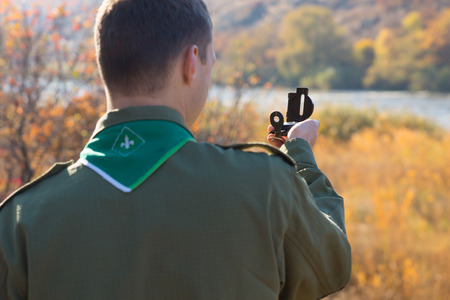 Scout taking a sighting with his compass facing out over a rural river using magnetic north to find his geographic location