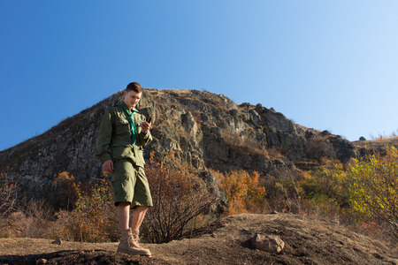 route master: Boy scout or ranger out on a wilderness trail in his uniform standing taking a compass reading to fix his location with a mountain peak behind Stock Photo
