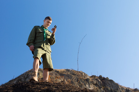 Scout using a magnetic compass to navigate as he explores the mountain wilderness standing on a cliff taking a reading of magnetic north, against a blue sky Stock Photo