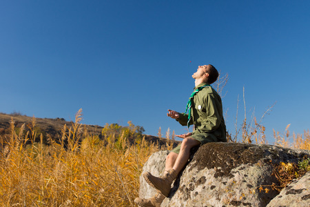 conservationist: Scout or ranger in uniform sitting on a rock in mountain grassland with his face turned up to the sun calling out as he enjoys a day in the wilderness