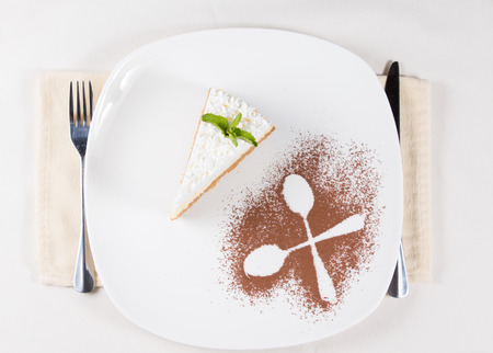 plating: Overhead view of an artistic plating of a slice of pie topped with cream served for dessert with the outlines of two crossed spoons in cocoa powder as a decoration