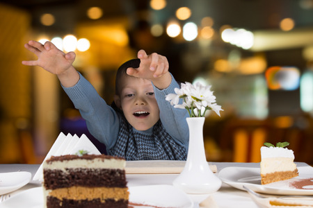 eager: Excited little boy reaching for a large slice of layered chocolate cream cake with a look of eager anticipation as he sits at table in a restaurant Stock Photo