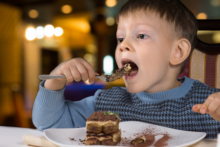 devouring: Little boy sitting at a table eating a big mouthful of delicious freshly baked chocolate cake Stock Photo