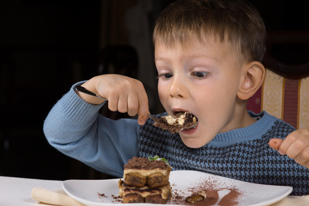 eager: Cute little boy eating chocolate cake about to take a big mouthful with a look of eager anticipation as he sits at table Stock Photo