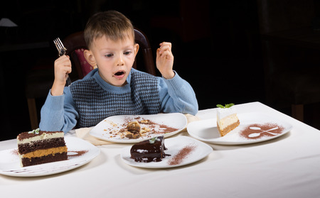 Excited little boy eyeing a choice of cakes laid out on the table in front of him as he makes a choice for his dessert