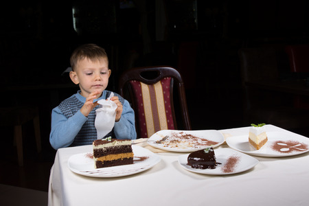 eager: Little boy finishing off a slice of cake at table laid with an assortment of cakes served on individual plates against a dark background Stock Photo