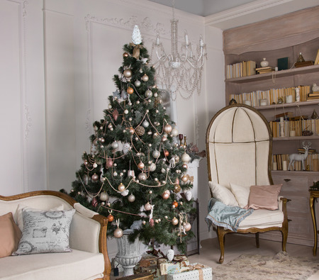 Decorated Christmas tree in an upmarket living room interior with classic vintage furniture Archivio Fotografico