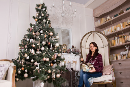 huge christmas tree: Young pretty woman sitting on large artistic holding presents, near huge Christmas tree decoration with various ornaments, while looking at the camera.