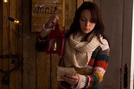 bundle of letters: Pretty young woman in stylish colorful winter knitwear, emptying the mail box at night reading the information on a bundle of letters tied with string by lantern light