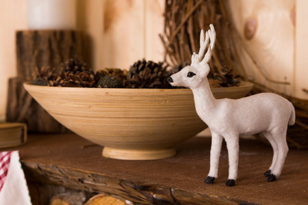 mantelpiece: Ornamental white Christmas reindeer decoration standing on a wooden mantelpiece alongside a ceramic bowl filled with pine cones