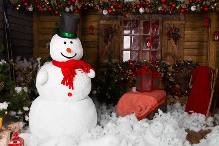christmas backdrop: Large indoor winter snowman on decorated wooden house with Cotton Snow on the Floor.