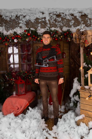 hanging around: Smiling Young Man Standing at the House with Plenty Christmas Decors in Winter Fashion Outfit, with Ice Skates Hanging Around his Neck, While Looking at the Camera.