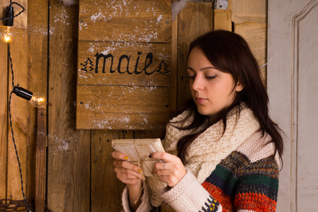 bundle of letters: Woman examining a bundle of letters tied with string from the mail box with a serious contemplative expression, side view Stock Photo