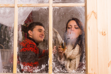 tryst: View through the cold frosted window of a young couple celebrating in a winter cabin enjoying a drink and blowing on the glass to condense their breath in the cold Stock Photo