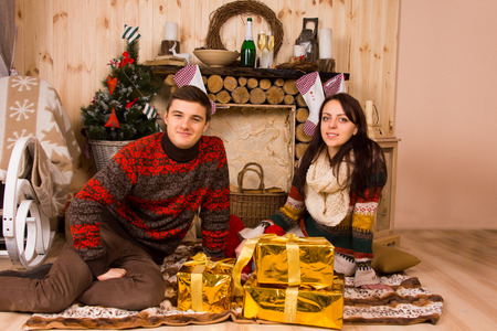 undoing: Young couple celebrating Christmas in a rustic cabin sitting on the floor on a rug in front of the hearth with stylish gold wrapped gifts smiling at the camera
