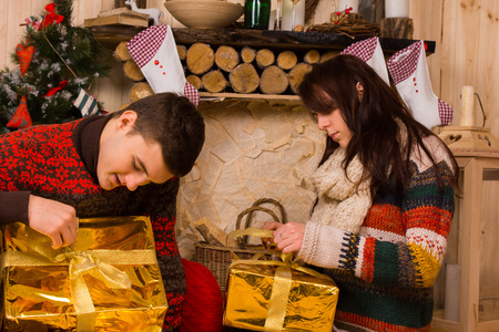 undoing: Young couple sitting on the floor in a rustic cabin opening festive gold Christmas gifts with eager anticipation