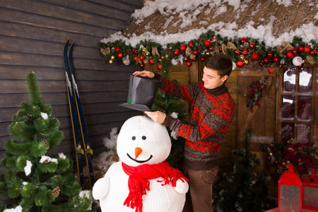 stock photo young white man in winter outfit putting a black hat on indoor snowman with red scarf at wooden house surrounded by christmas ornaments