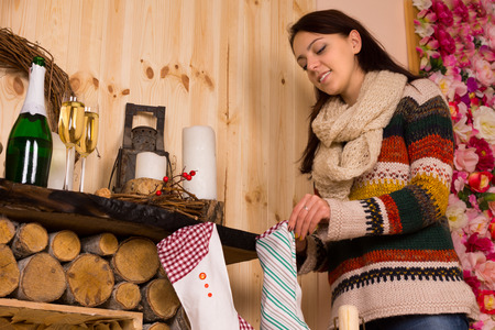mantelpiece: Young woman filling Christmas stockings in a rustic wooden cabin hanging on the hearth with a bottle and glasses of champagne on the mantelpiece