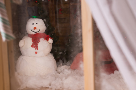 window display: Christmas snowman viewed through a frosted window with open curtain standing in the winter snow outside in the darkness Stock Photo