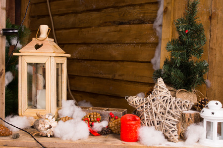 entwined: Rustic Christmas still life with handcrafted decorations including a wooden lantern, star of entwined twigs, candles and kapok snow in the interior of a wooden cabin or hut