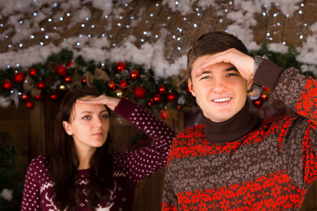 st nick: Couple Wearing Sweaters Looking into the Distance Outdoors in Winter in front of Log Cabin Stock Photo