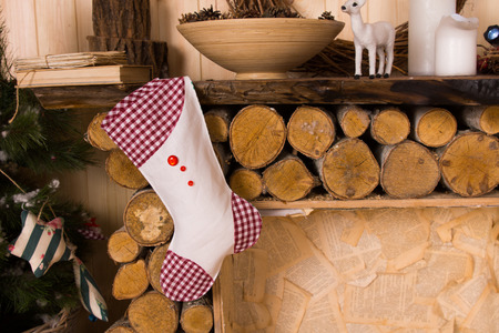 Gingham Christmas Stocking Hanging from Rustic Wooden Fireplace Mantle